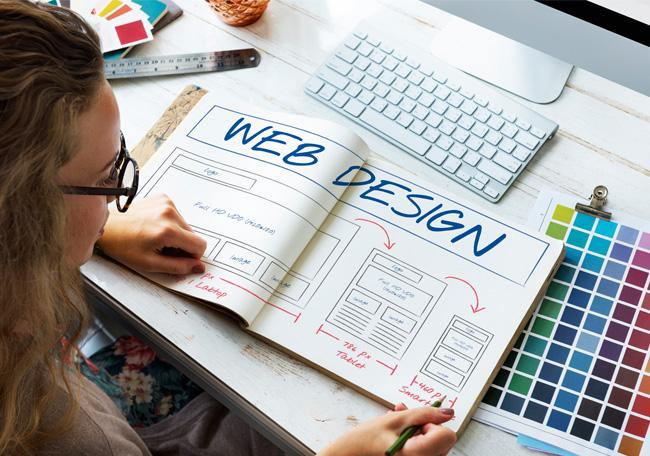 woman looking at web design book
